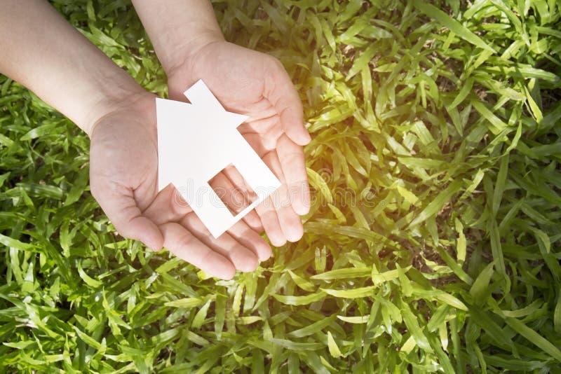 Casa della tenuta della mano contro il campo verde fotografia stock libera da diritti