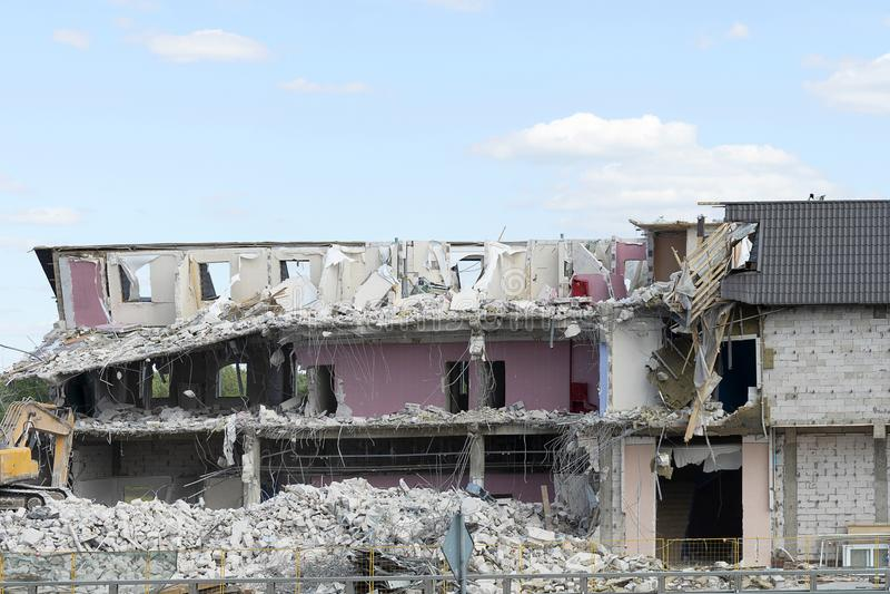 A casa destruída, assoalhos quebrados, destruiu as paredes e o telhado Uma máquina escavadora demole uma construção do multi-anda foto de stock royalty free