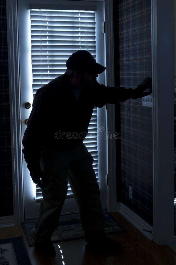 Casa di Breaking In To dello scassinatore di notte alla parte posteriore da parte a parte fotografie stock libere da diritti