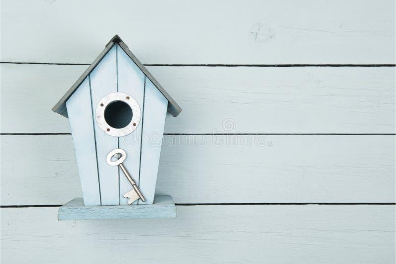 Casa di legno blu dell'uccello con una chiave del metallo su un backgro di legno blu immagini stock libere da diritti