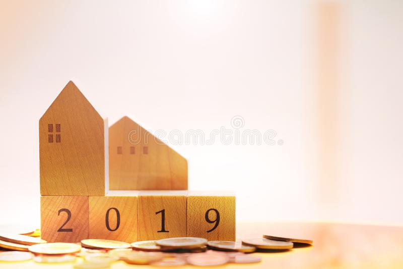 Casa di legno con i numeri di blocco dell'anno 2019 che circonda dal mucchio delle monete immagine stock libera da diritti