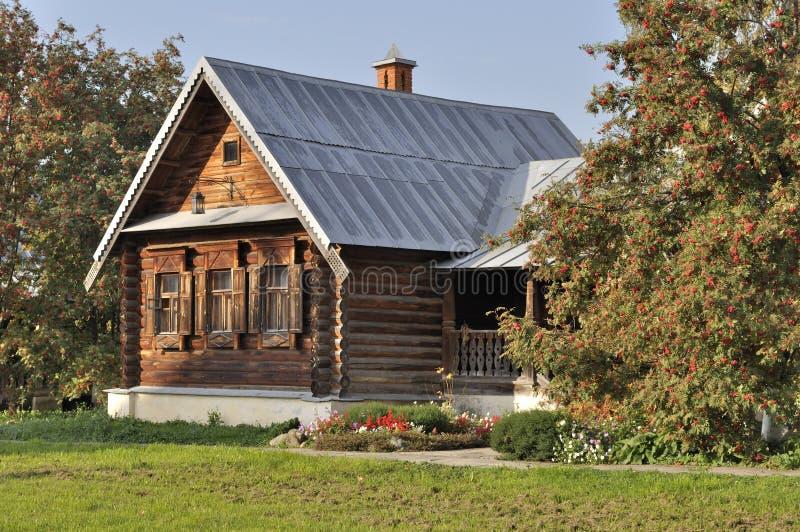 Casa di legno con il portico e gli sorba-alberi immagini stock