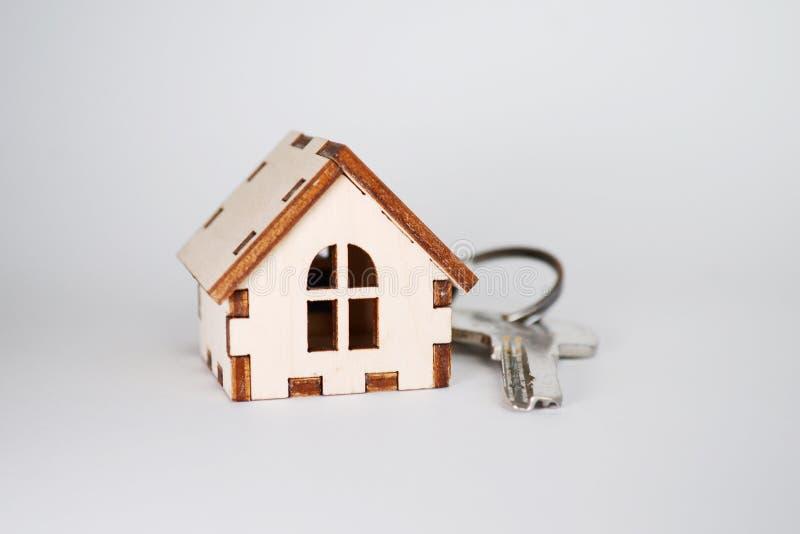 Casa di legno con la chiave su fondo grigio, concetto per la vendita delle case con copyspace immagine stock libera da diritti