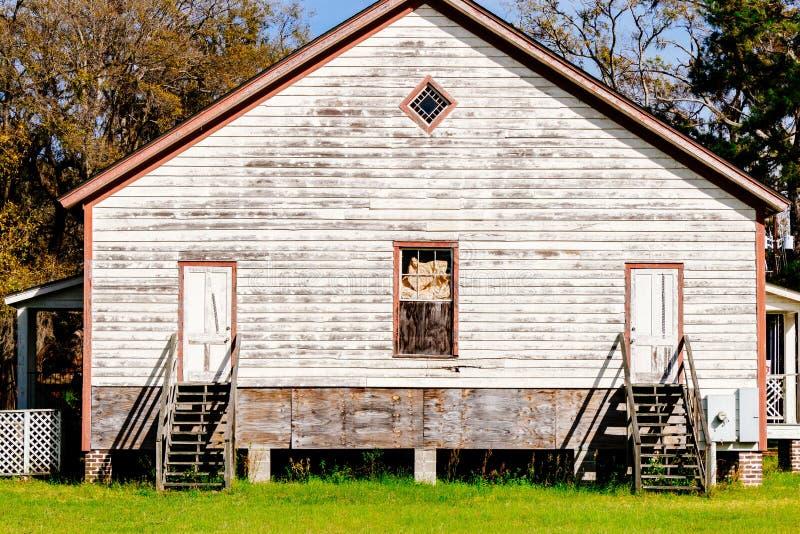 Casa di legno costruita in un grande campo verde fotografia stock