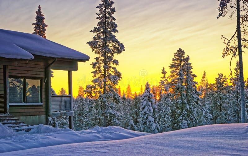 Casa di legno del cottage al tramonto di inverno fotografia stock libera da diritti
