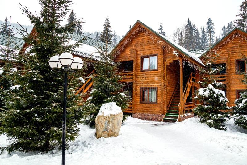 Casa di legno del cottage nella località di soggiorno di montagna Paesaggio di inverno di natale Il bello cottage dell'inverno ha fotografie stock