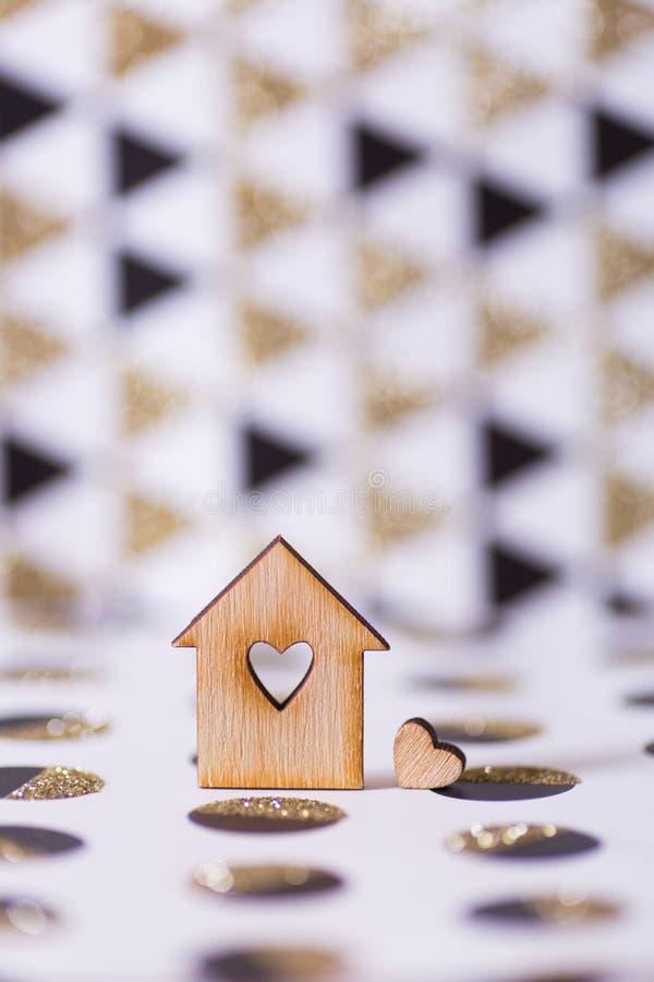 Casa di legno del primo piano con il foro nella forma di cuore su fondo astratto geometrico con scintillio dorato immagine stock libera da diritti