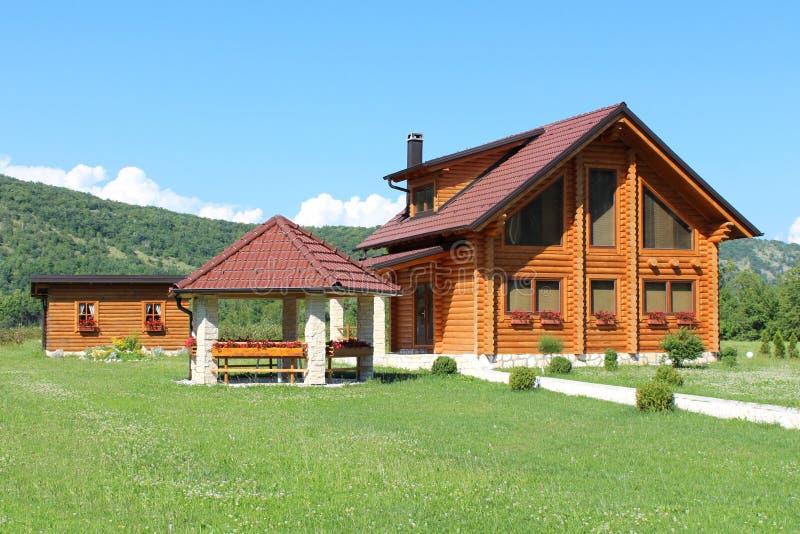 Casa di legno della cabina di ceppo con il gazebo di pietra e tettoia di legno dello strumento fotografia stock libera da diritti