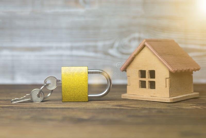 Casa di legno e serratura chiusa, su un fondo di legno immagine stock