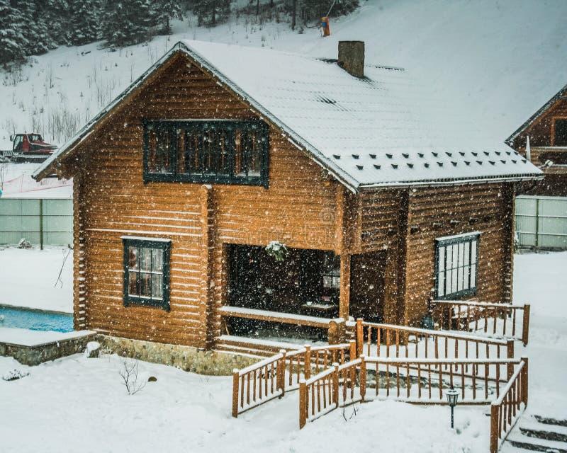 casa di legno di inverno in neve immagine stock