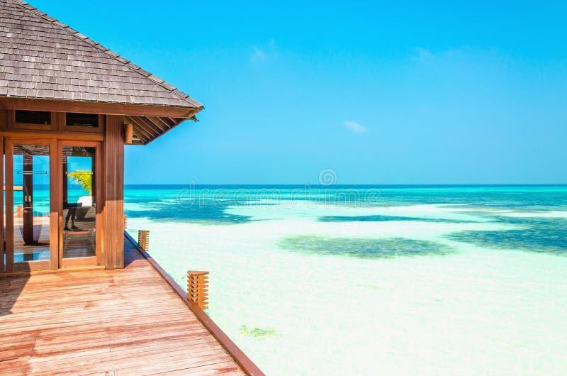 Casa di legno di lusso sui trampoli sui precedenti di acqua azzurrata e di bello cielo soleggiato fotografie stock