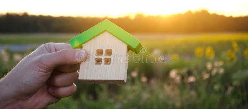 Casa di legno nelle mani nei precedenti di tramonto Concetto 6 del bene immobile Casa amichevole di Eco Simbolo di vita familiare fotografie stock