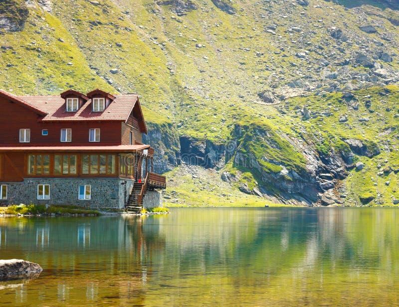 casa di legno rossa sul lago del ghiacciaio immagini stock