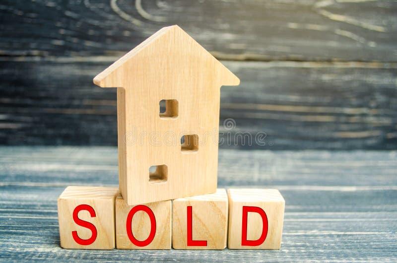 Casa di legno su un fondo nero con l'iscrizione venduta vendita della proprietà, casa, bene immobile Alloggiamento acquistabile P fotografia stock libera da diritti