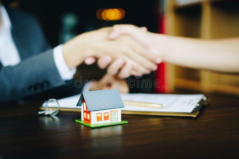 Casa di legno sui precedenti della tavola con gli agenti immobiliari ed il cliente che stringono le mani dopo la firma del contra fotografia stock libera da diritti