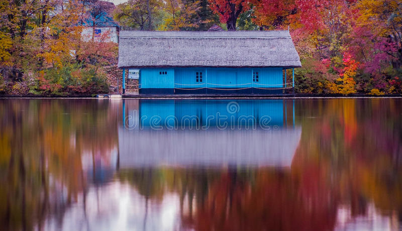 Casa di legno sul lago nella stagione di autunno fotografia stock