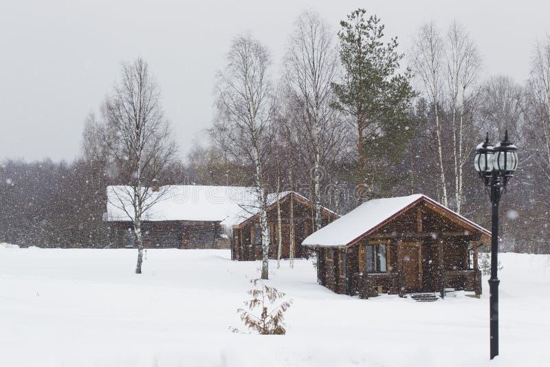 Casa di legno tre nell'inverno sotto la neve immagini stock