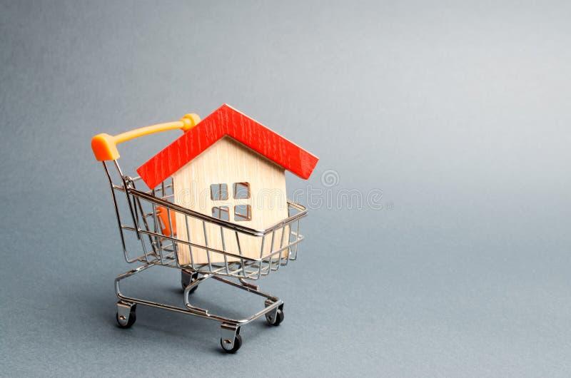 Casa di legno in un carrello del supermercato Il concetto di acquisto una casa o dell'appartamento Alloggiamento acquistabile Pre immagini stock libere da diritti