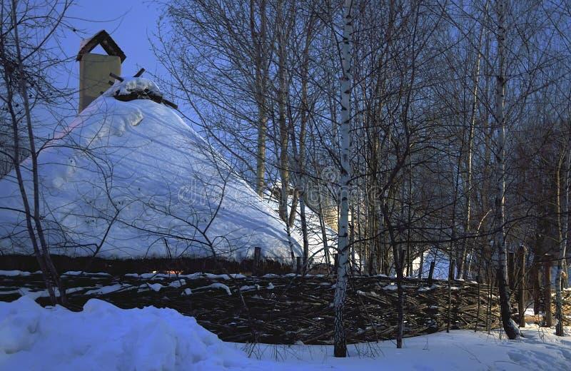 Casa di legno in una foresta di inverno sotto un cappuccio della neve immagini stock