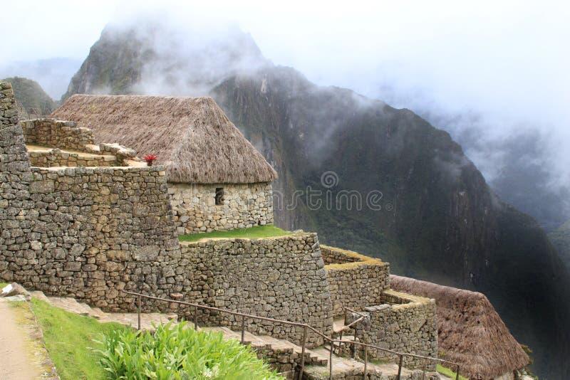 Casa di Machu Picchu e montagne nuvolose immagini stock libere da diritti