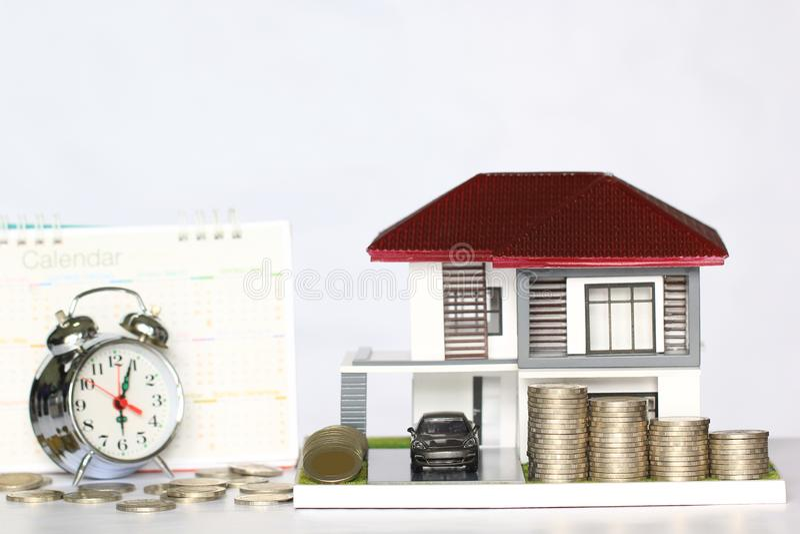 Casa di modello di concetto di tempo di imposta, ed automobile con l'impilamento dei soldi delle monete fotografia stock libera da diritti