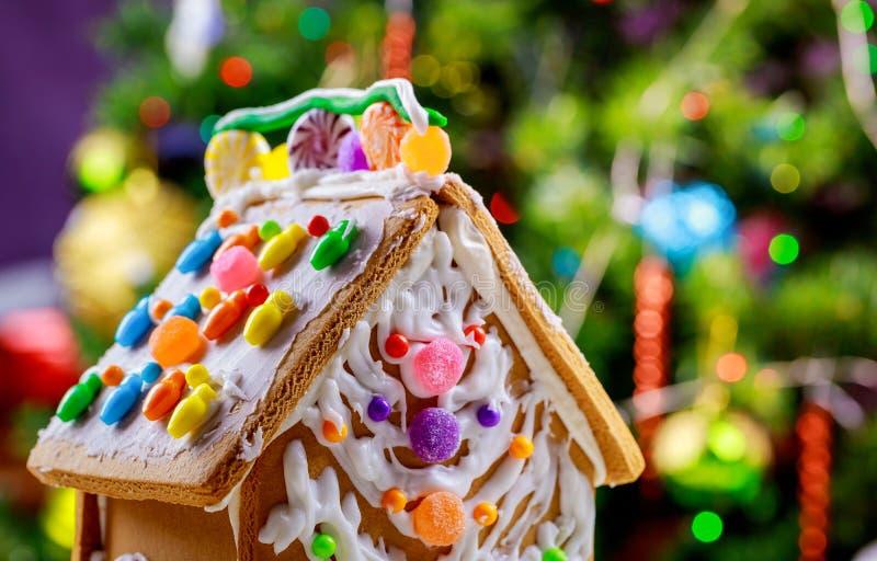 Casa di pan di zenzero con la condizione della glassa sulla tavola con l'albero di Natale delle decorazioni fotografie stock libere da diritti