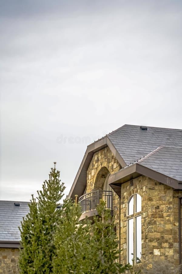 Casa di pietra con il balcone del semicerchio e giro quarto con la finestra estesa della gamba immagini stock libere da diritti