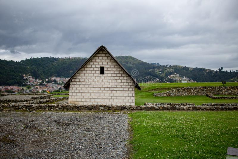 Casa di pietra fatta a mano in un grande bello campo verde con il cielo nuvoloso nei precedenti fotografia stock libera da diritti