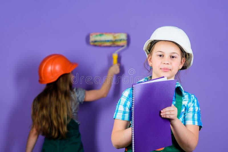 Casa di rinnovamento felice dei bambini Ridipinga le pareti Attività di miglioramento domestico Ragazze dei bambini che progettan immagine stock libera da diritti