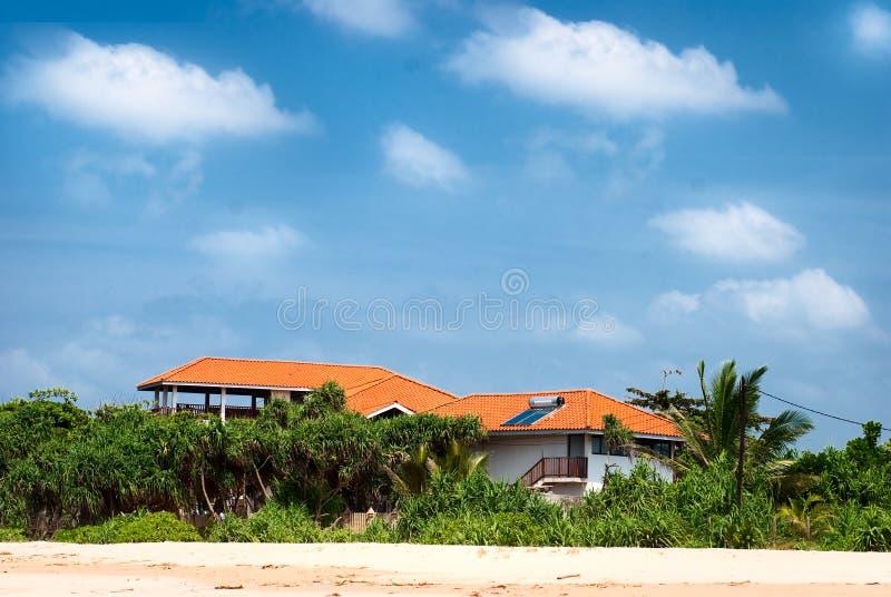Casa di spiaggia con i comitati solari e la foresta tropicale fotografia stock libera da diritti