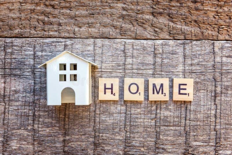 A casa diminuta do modelo do brinquedo com CASA da inscrição rotula a palavra no fundo de madeira fotos de stock royalty free