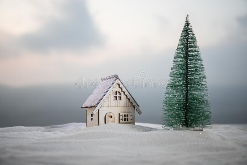 Casa diminuta do Natal e do ano novo na neve na luz solar Pouco casa do brinquedo na neve com árvore Fundo festivo foto de stock