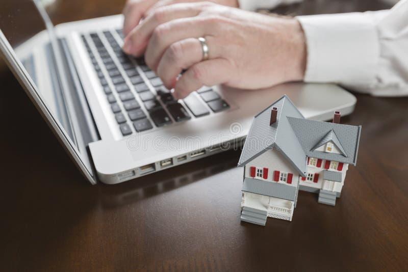 Casa diminuta perto do homem que datilografa no laptop imagem de stock