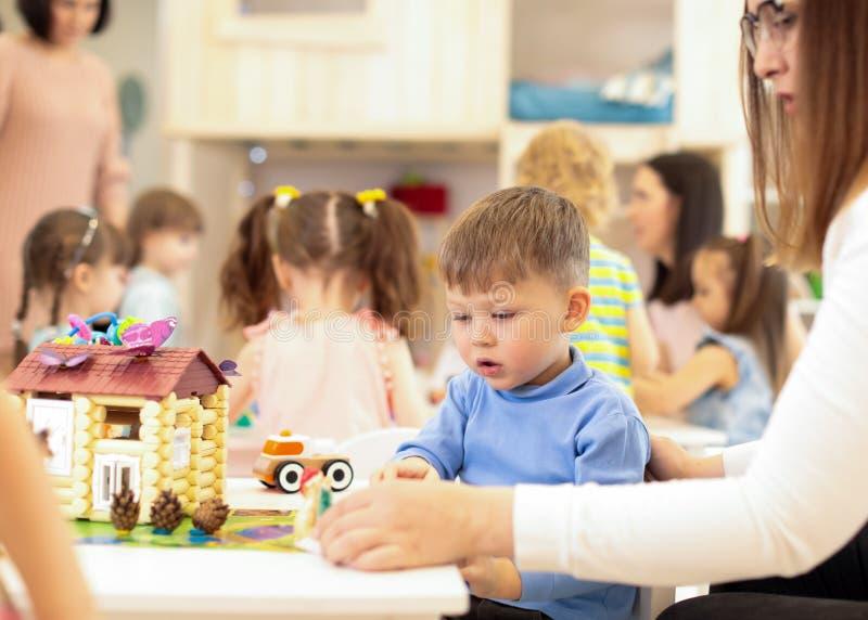 Casa do brinquedo da construção do menino da criança do jardim de infância na sala de jogos no pré-escolar, conceito da educação fotografia de stock royalty free