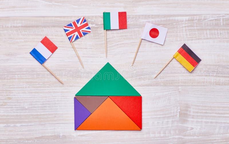Casa do enigma do tangram com as bandeiras dos países fotografia de stock