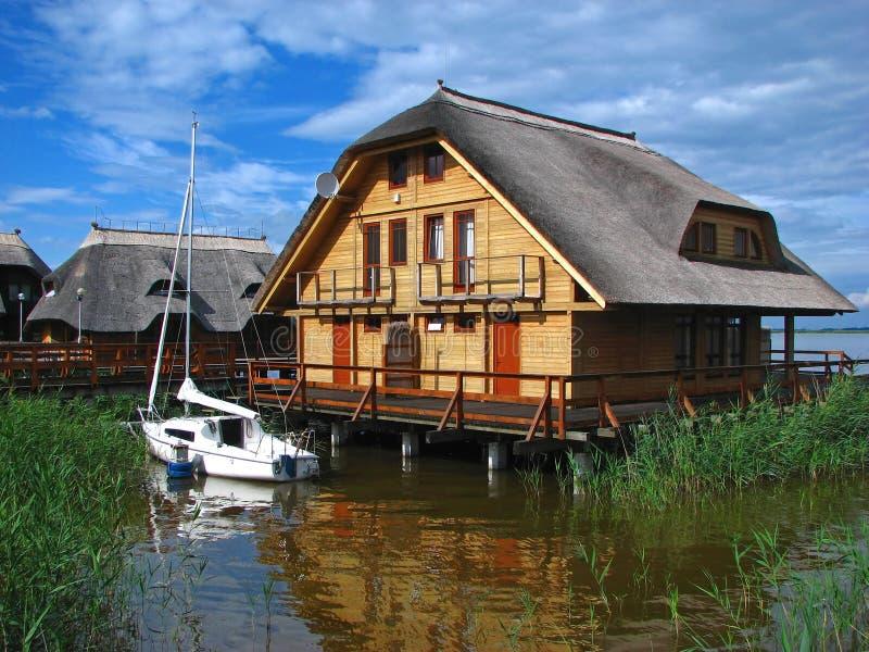 Casa do fim de semana na água com barco foto de stock royalty free