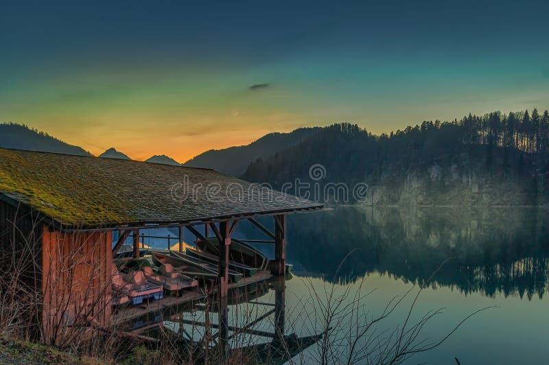 Casa do lago com um cais pequeno na frente das montanhas imagem de stock royalty free