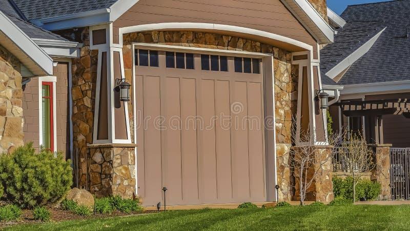 Casa do panorama com gramado dianteiro da porta da garagem e porta do metal vista contra o céu azul claro imagem de stock