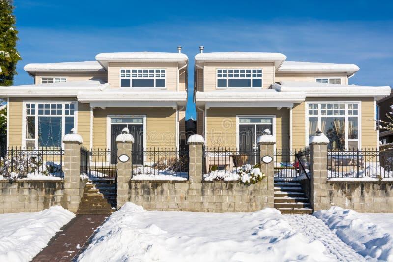 Casa a dos caras residencial con el jardín en nieve el día soleado del invierno en Canadá fotografía de archivo libre de regalías