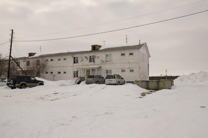 Casa dos-famosa vieja en invierno con nieve, coches y árboles en la yarda Pobreza y miseria, del norte fotos de archivo libres de regalías
