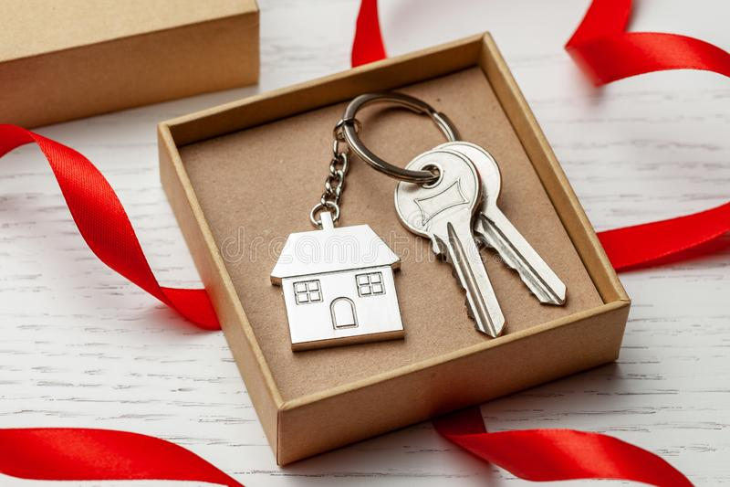 Casa e chiavi di Keychain con la scatola rossa di regalo e del nastro su fondo di legno bianco immagine stock libera da diritti