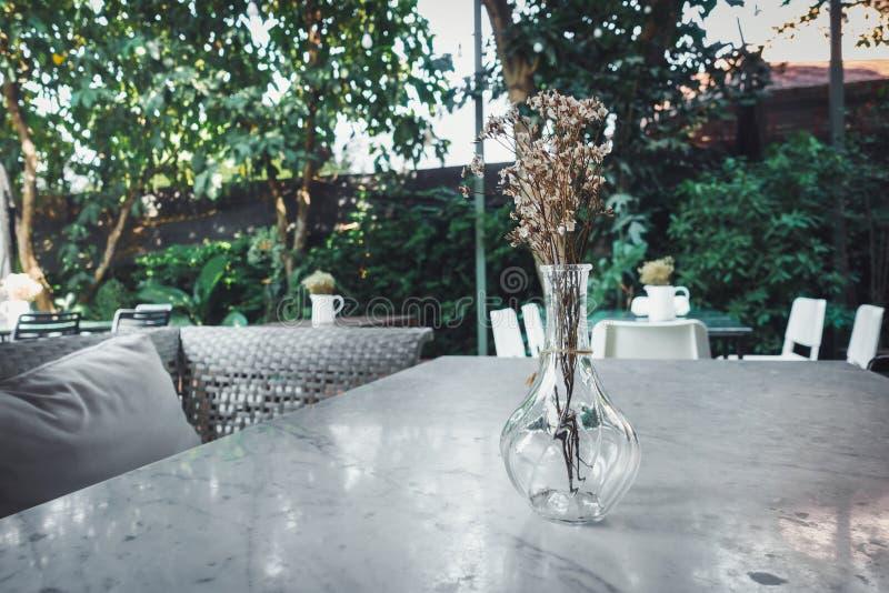 Casa e decoração de jardinagem exterior com ramalhete em uma disposição de vidro do vaso na mesa da tabela do granito , Loja da c fotografia de stock