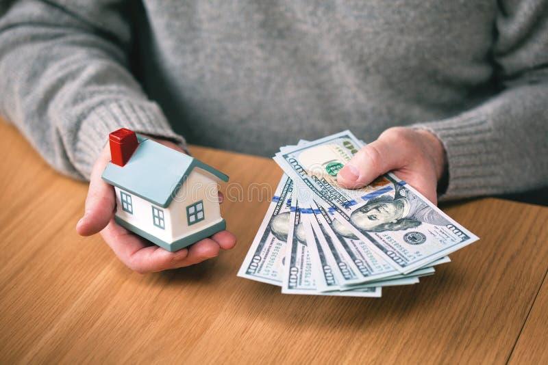 Casa e dinheiro compre bens imobiliários, hipoteca sobre a casa mãos que guardam contas de cem-dólar e a casa novas do brinquedo fotos de stock