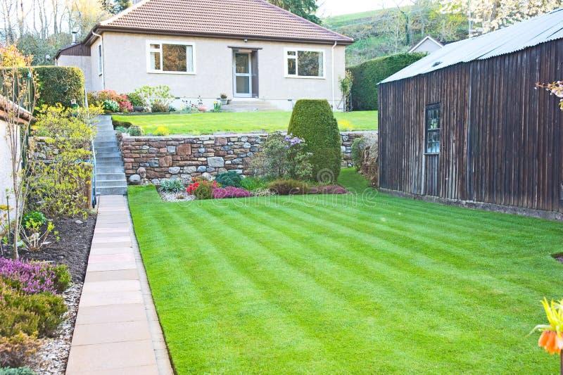 Casa e gramado listrado imagem de stock