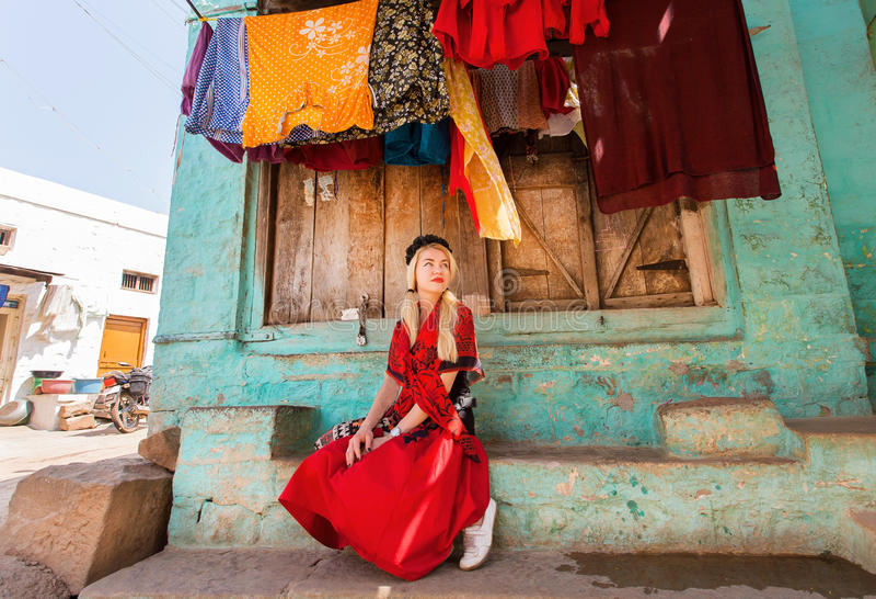 Casa e jovem mulher da vila que sentam-se na parte dianteira da construção colorida na cidade indiana pequena fotos de stock royalty free