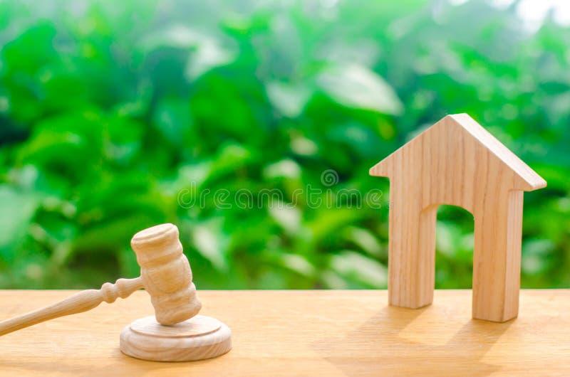 Casa e martello di legno del giudice su un fondo verde Proprietà di prova di concetto La decisione del Tribunale sul trasferiment fotografie stock