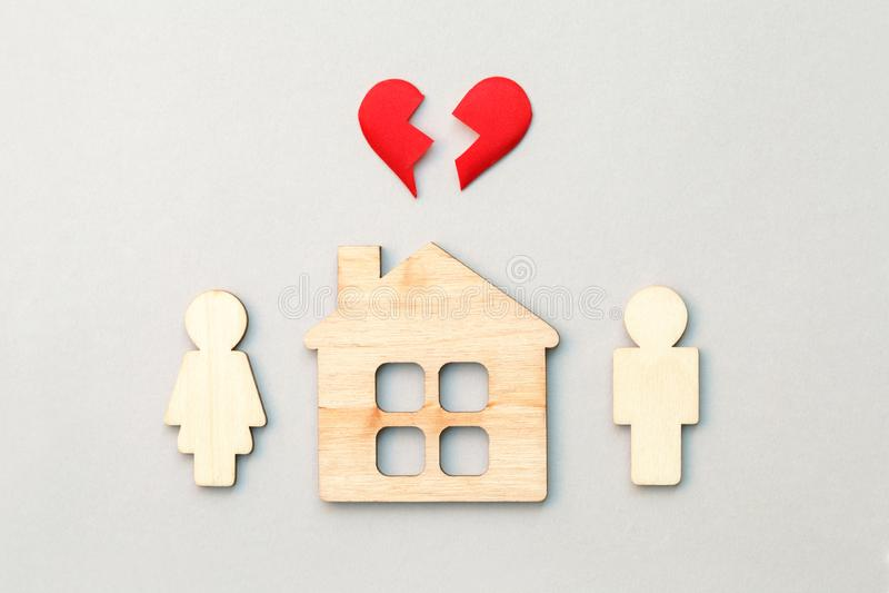 Casa e modelos de madeira do homem e da mulher com coração quebrado vermelho, divórcio, fim do relacionamento e conceito da união imagem de stock