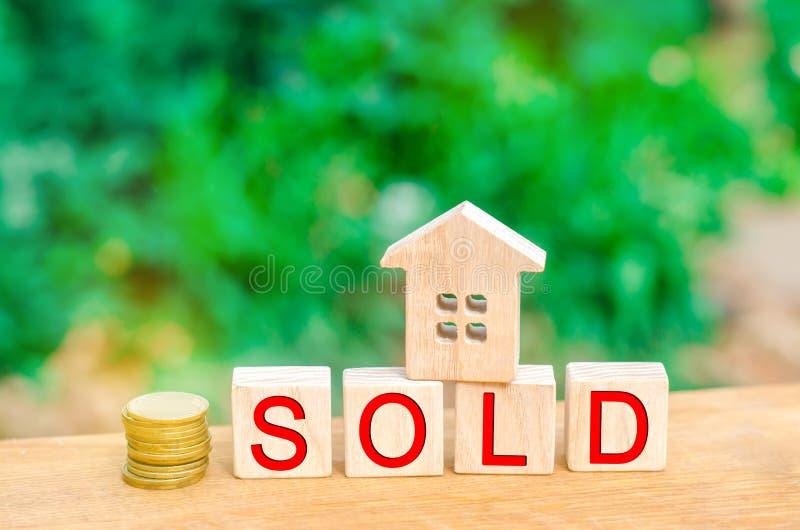 Casa e monete di legno con il ` venduto ` dell'iscrizione vendita della proprietà, casa, bene immobile Alloggiamento acquistabile fotografie stock