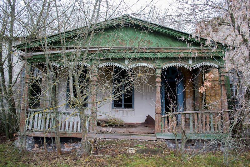 A casa e o patamar velhos, negligenciados, lordly entre as árvores Textura da madeira rachada velha pintada verde imagens de stock royalty free