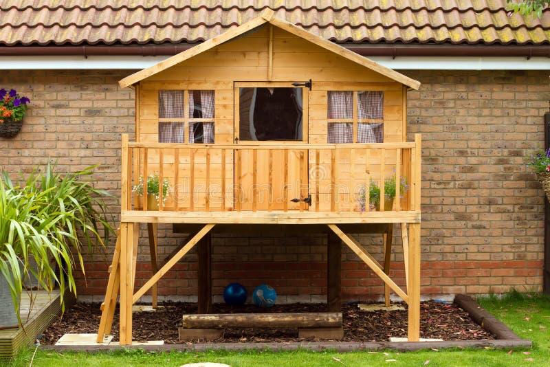 Casa em a árvore de madeira das crianças no jardim fotografia de stock